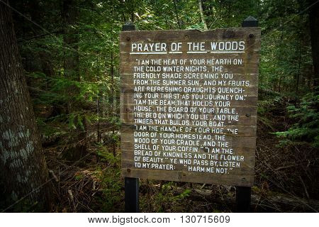Newberry, Michigan, USA - May 5, 2016: Prayer Of The Woods poem engraved on a wooden sign with a wilderness forest background. Taken on the North Country Trail in Tahquamenon Falls State Park.