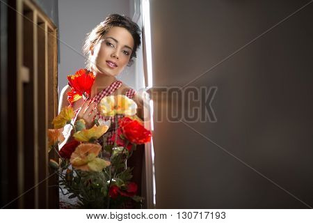 Romantic smiling girl in red and white dress looks into the camera while holding flowers. She sat down in the aisle between the light walls and a table. Light falls from the left. Horizontal.