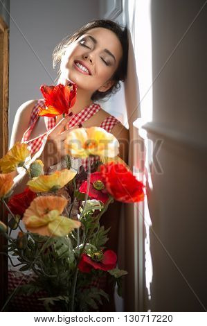 Dreamy smiling girl in red and white dress with closed eyes holding flowers. She leans her head on the wall. She sat down in the aisle between the light walls and a table. Light falls from the left. Vertical.