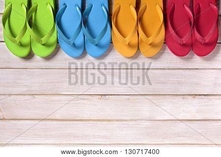 Row of flip flops on beach wood decking
