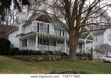 HARBOR SPRINGS, MICHIGAN / UNITED STATES - DECEMBER 24, 2015: A large Victorian home with a wraparound porch below the bluff on Fourth Street in Harbor Springs, Michigan.