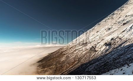 Mountain partially covered with snow soars above the clouds.
