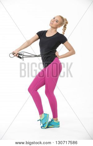 Pretty smiling blonde in the sportswear stands on the white background in the studio. She wears cyan-yellow sneakers, pink pants and black t-shirt. She stretched a skipping rope with her hands. Left hand is on her hip, while right hand pulls the skipping