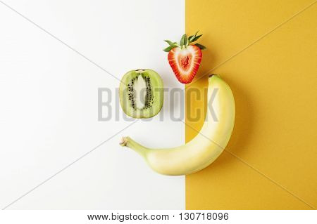 Kiwi strawberry banana on yellow white background, fruits summer