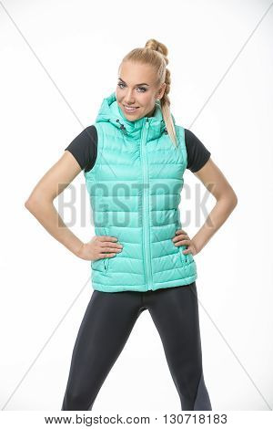 Young blonde girl in the sportswear stands on the white background in the studio. She wears black-gray pants, black t-shirt and mint vest. She holds her hands on her waist. She has a plait on her head. She looks into the camera with a smile. Vertical.