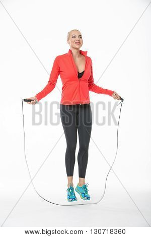 Sportive blonde girl in the sportswear jumps with skipping rope on the white background in the studio. She wears cyan-yellow sneakers, black pants, black t-shirt and red hoody. Her feet are off the floor. She looks up with a smile. Vertical.