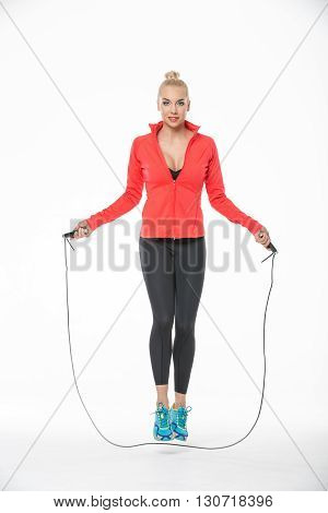 Young blonde girl in the sportswear jumps with skipping rope on the white background in the studio. She wears cyan-yellow sneakers, black pants, black t-shirt and red hoody. Her feet are off the floor. She looks into the camera with a smile. Vertical.