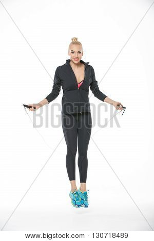 Beautiful blonde girl in the sportswear jumps with skipping rope on the white background in the studio. She wears cyan-yellow sneakers, black pants, pink-black t-shirt and black hoody. Her feet are off the floor. She looks into the camera with a smile. Ve
