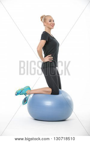 Pretty blonde girl in the sportswear is on the blue fitball on the white background in the studio. She wears cyan-yellow sneakers, black pants and black t-shirt. She looks to the side with a smile. Shoot sideways. Vertical.