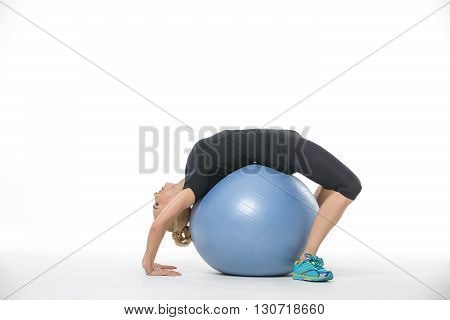 Cute blonde girl in the sportswear with a blue fitball on the white background in the studio. She wears cyan-yellow sneakers, black pants and black t-shirt. She makes a bridge while she lies on the fitball. Photographed sideways. Horizontal.