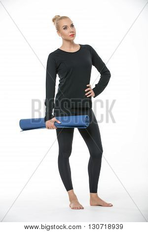 Young blonde girl in the sportswear stands barefoot on the white background in the studio. She wears black pants and black long sleeve t-shirt. She holds a blue gymnastic mat in the right hand. Her left hand is on the waist. She looks up. Vertical.