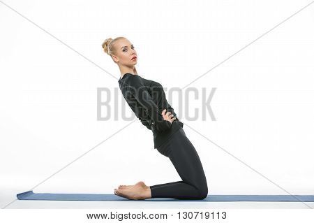 Blonde girl in the sportswear stands on the knees on a blue gymnastic mat on the white background in the studio. She wears black pants and black long sleeve t-shirt. She is barefoot. Her hands are on the waist. She tilts her body back. She looks into the