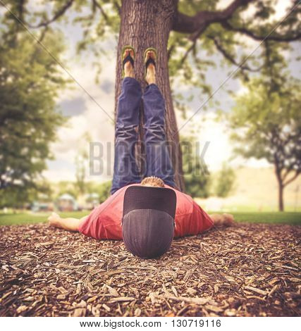 a man with his feet resting on a tree trunk during summer toned with a vintage retro instagram filter effect app or action