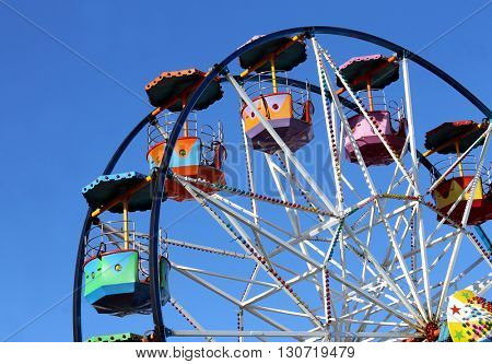 Colorful ferris wheel with blue sky background.