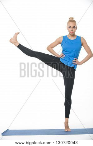 Sportive blonde girl in the sportswear stands on the left leg on a blue gymnastic mat on the white background in the studio. She wears black pants and blue sleeveless t-shirt. She is barefoot. She holds her hands on the waist. Her right leg raised and str