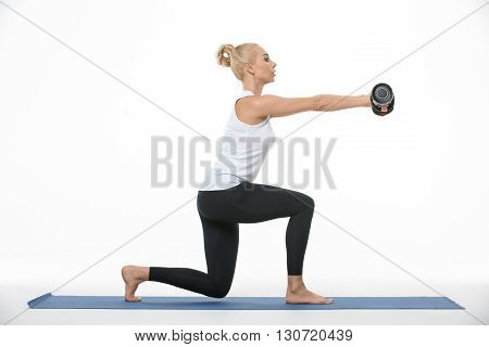 Sportive blonde girl in the sportswear with dumbbells in her hands does split squats on a blue gymnastic mat on the white background in the studio. She wears black pants and white sleeveless t-shirt. She is barefoot. Her hands are raised. She looks forwar