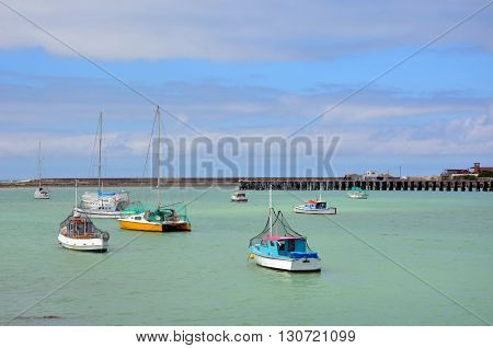 Colourful fishing boats in turquoise harbour waters