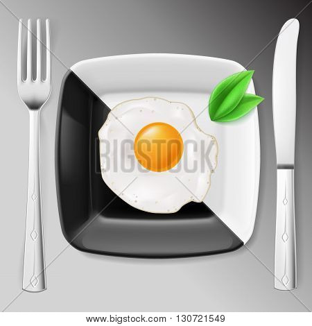 Served breakfast. Fried egg on black and white plate served with fork and knife