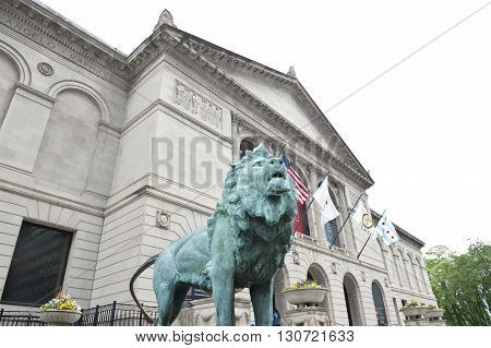 The Art Institute of Chicago located in Grant Park, which is a encyclopedic art museum. The green lion statue in front of the building along with American flags is seen.