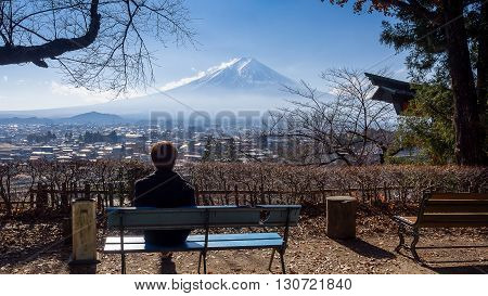 A man sitting on a bench seeing Mt. Fuji with clear sky alone