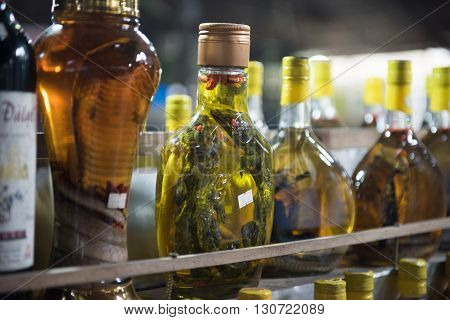 Alcoholic beverages being sold with snakes and frogs inside the bottle in a market in Cai Be, Vietnam. These drinks include vodkas, whiskey and are pretty popular among the locals.