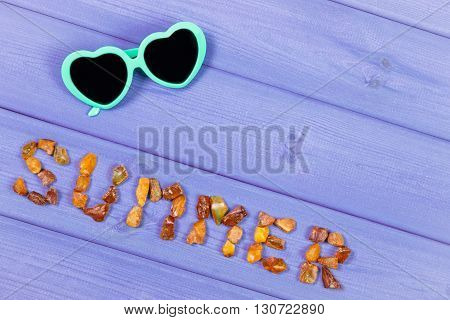 Inscription summer made of amber stones and sunglasses on purple boards summer and vacation time copy space for text