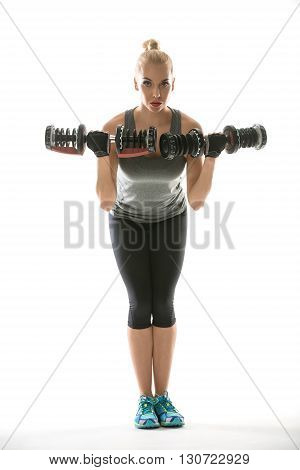 Pretty blonde girl in the sportswear with dumbbells in her hands stands on the white background in the studio. She wears cyan-yellow sneakers, black pants, gray sleeveless t-shirt and dark sports gloves. Her hands are raised near her torso which tilted fo
