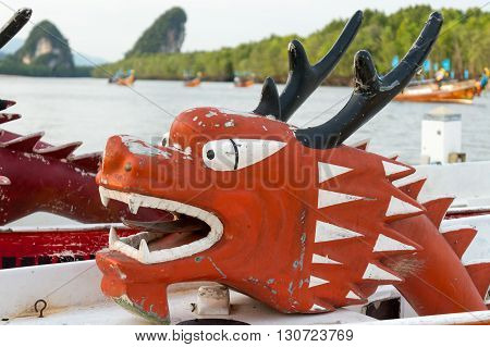 Red Dragon Head on a race Boat during a Racing Event in Krabi with beautiful karst rocks in the backround.