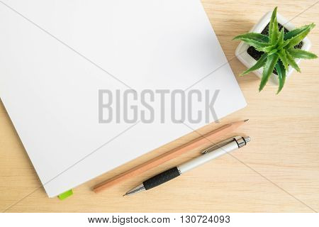 Top view of office desk table with open notebook pencil pen and small tree in a white pot on wood table