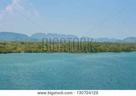 View on the Mainland of Thailand from Koh Lanta with beautiful mangrove forests and mountains close to the ocean.