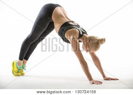 Athletic blonde girl in the sportswear leans on her hands and toes on the white background in the studio. She wears yellow-cyan sneakers, mint socks, black pants and black top. Her pelvis is raised. She looks at the floor. Photographed from the side. Hori