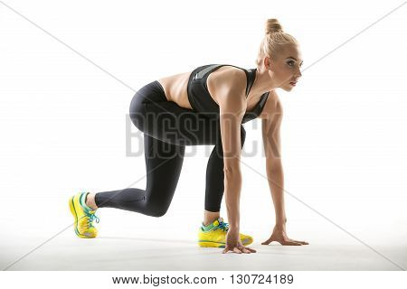 Beautiful blonde girl in the sportswear does split squats on the white background in the studio. She wears yellow-cyan sneakers, mint socks, black pants and black top. She presses her torso to the right knee and the hands presses to the floor. She looks f