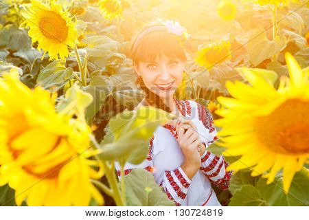 Pretty young woman in national ukrainian blouse embrodery looking to camera on a sunflower plant at sunset backlight.