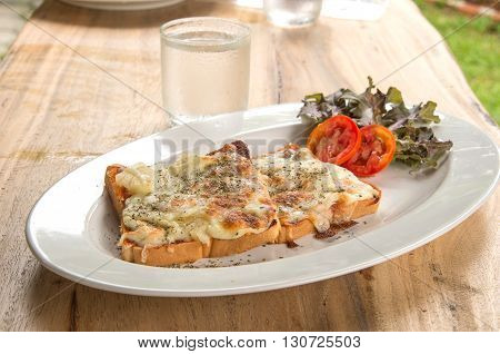 Pizza Toast Glass of water placed on wooden table.