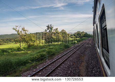 View from a running train while travelling to Bangkok. On the background, lush green fields and mountains are seen on a clear, bright day. Rail is an important transportation mode in Bangkok.