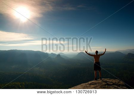 Climber In Black Pants. Gesture Of Triumph. Body Naked Man On The Peak Of Sandstone Rock In National