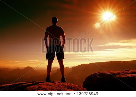 Red Filter Photo. Slim Tourist In Pants On The Cliff Of Rock Empire Is Watching Down To Valley. Hot