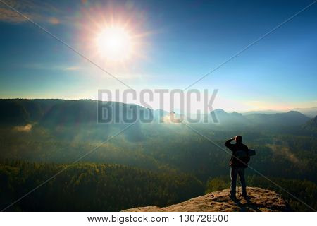 Tourist With Backpack And Poles On  Rocky Peak. Sunny Day, Dreamy Fogy Valley Below
