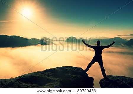 Funny Jumping Hiker In Black Celebrate Triumph. Stay Between Two Rocky Peaks. Wonderful Misty Daybre