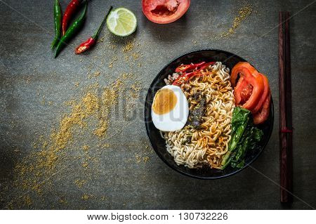 Instant noodles with spicy seasoning vegetables and salted egg. Top view.