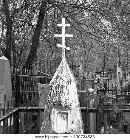 Very old abandoned cemetery in the woods, abandoned grave with a white cross