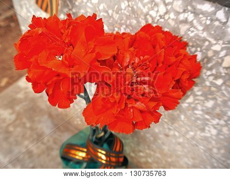 Red carnations with black and gold ribbon