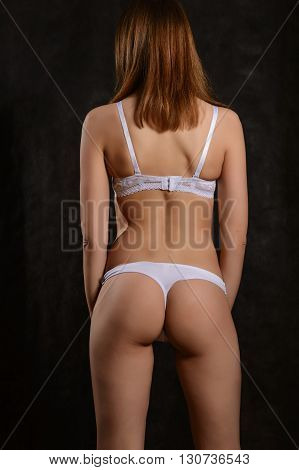 girl in white underwear back on a black background