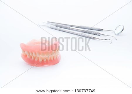 Denture and dental toolsdental mirror on white background