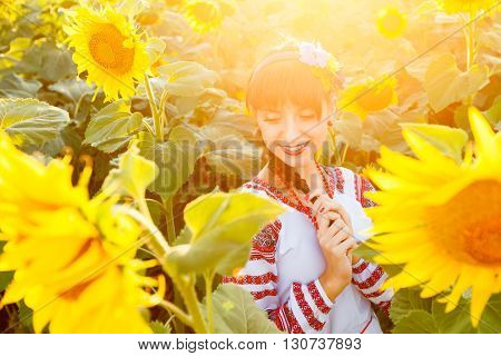 Beautiful young woman in national ukrainian blouse embrodery with closed eyes on a sunflower field at sunset backlight.