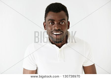 Handsome African American Male Looking At The Camera In Astonishment, Surprised With Incredible Stor