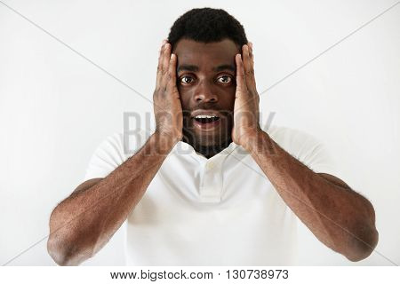 Close Up Shot Of Shocked Handsome Dark Skinned Student Male Wearing White T-shirt Looking In Full Di