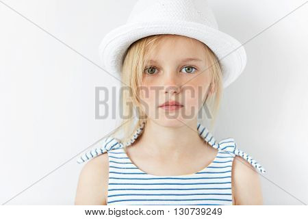 Cute Preschool Girl With Green Eyes And Blonde Hair Wearing Striped Dress And White Hat Looking At T