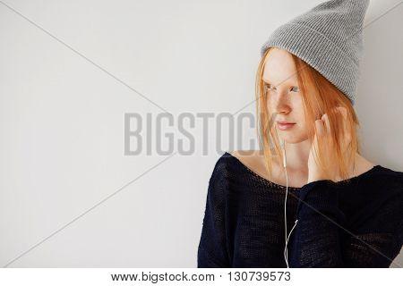Redhead Teenage Girl Wearing Hipster Cap Listening To Her Favorite Music With Earphones. Pretty Scho