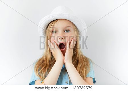 Headshot Of Pretty Surprised Little Girl Wearing White Hat And Denim Shirt With Hands On Cheeks Look